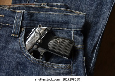 Gun in a pocket of jeans trousers fighting loaded. Pistol in the pocket of jeans.