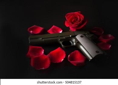 Gun and red rose on dark background