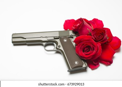 Gun with red roses on black backdrop
