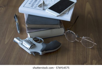 Gun and school items, textbook is fake title