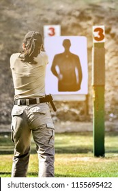Gun shooting competition. Lady shooting with gun at target in shooting range.