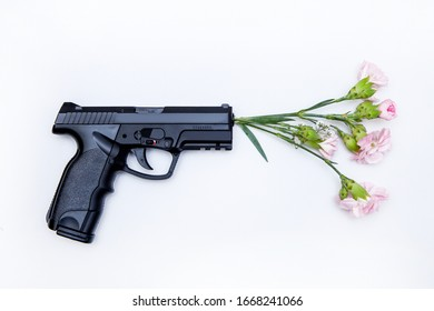 The gun shoots flowers. Weapon creative idea.Top view on white isolated background.