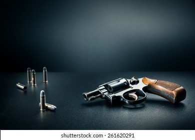 gun sitting on a table with bullet shells