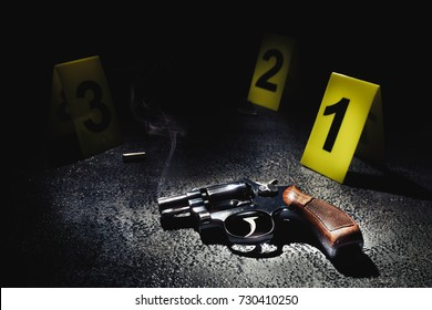 gun with smoke on the floor and evidence markers / high contrast image