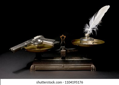 Gun and white feather pen on a weight scale. Concept knowledge versus violence. Isolated on dark background. With copy space text. Studio Shoot.