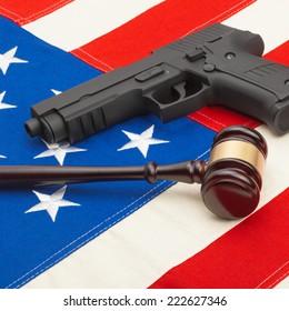 Gun and wooden judge gavel over USA flag - studio shoot - 1 to 1 ratio