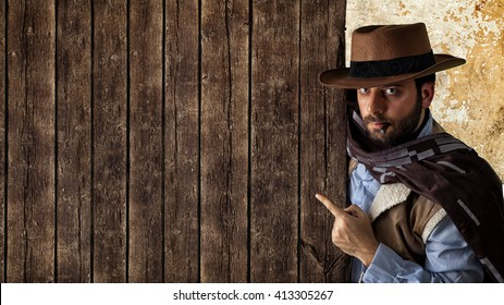 Gunfighter of the wild west pointing on wooden table.