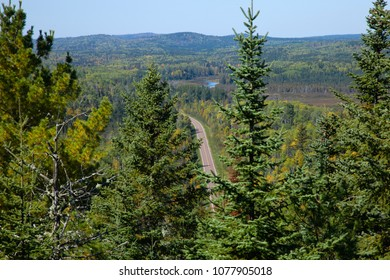 The Gunflint Trail in northern Minnesota viewed between pines from a high hill