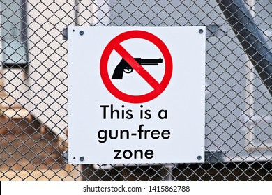 A Gun-free zone signpost on a fence. Gun control in America concept image.