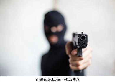 The gunman killer was aiming his gun at the target, robbery, crime, kidnapping