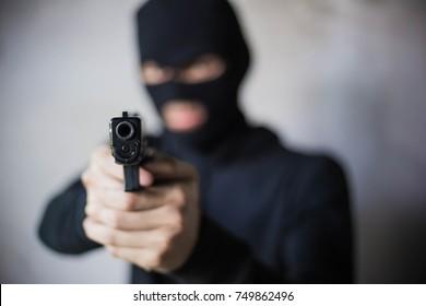 Gunman/Man carrying a gun wearing a black mask. And aim at the goal.