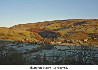 Gunnerside, Swaledale, Yorkshire Dales National Park, North Yorkshire, England, Britain, December 2019, early morning light striking hills above the Yorkshire Dales village of Gunnerside