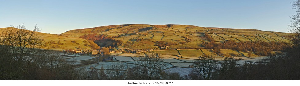 Gunnerside, Swaledale, Yorkshire Dales National Park, North Yorkshire, England, Britain, December 2019, panorama of early morning light striking hills above the Yorkshire Dales village of Gunnerside