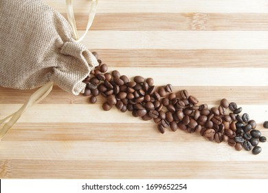 Gunny sack with coffe beans on a wood board.