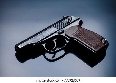 Guns and ammunition. Pistol on a dark background