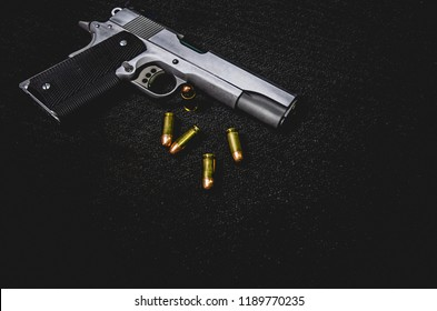 Guns and ammunition are placed on a black background. Monochrome tone.