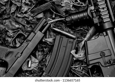 Guns, Weapons and military equipment for army, Assault rifle gun (M4A1) and 9mm pistol on dry leaves forest background.