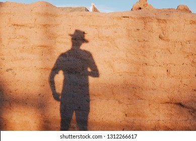 Gunslinger, cowboy silhouette in the sunset ready for a duel
