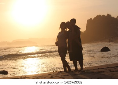 Gunungkidul, Jogjakarta, Indonesia - June 13, 2019 : A happy family captured enjoying sunset panorama at Indrayanti Beach, Jogjakarta, Indonesia.