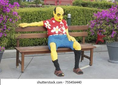 GUNZBURG, GERMANY - June 25, 2014: Made Lego bricks Man sitting on a bench, LEGOLAND
