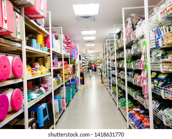 Gurgaon, Delhi, India - circa 2019: white supermarket shelves with insulated bottles and bowls like sponges, brushes, wipes. Also visible are customers shopping in the distance