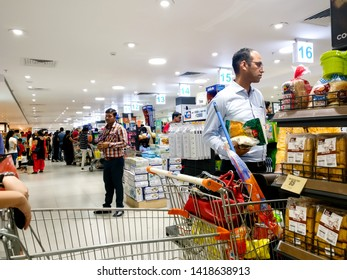Gurgaon, Delhi, India - circa 2019: Shoppers standing in line to bill and checkout in modern hypermarket store. The point of sale impulse products are clearly visible as customers stand with their