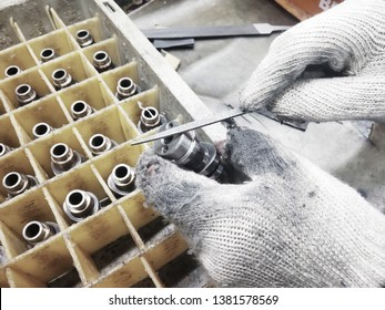 Gurgaon/ Gurugram, Haryana, India - April, 2019: Removing the dent and scratch on spare part of engine(Camshaft) . Man removing Burr on part  with file.
