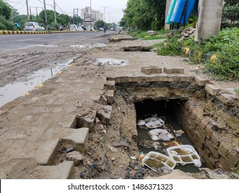 Gurgaon, Haryana, India - 07/25/2019: Broken roadside walkway exposes underground sewage filled with rain water, plastic waste and food trays thrown inside a gutter on an overcast day in monsoon.