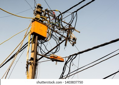 Gurgaon, India - circa 2019 : Tangled wires on a pole with a yellow circut box and a street light. These wire tangles pose a safety and fire hazard owing to the large number of legal and illegal