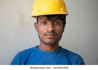 Gurgaon, India - May 14 2019: Portrait of a labourer with the helmet working at an urban construction site.