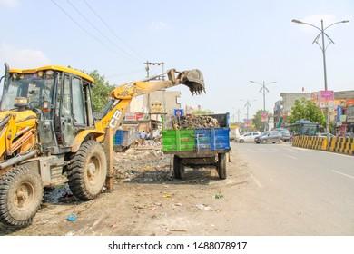 Gurgaon/Gurugram, Haryana, India - 21 July, 2019: Crane working at roadside in gurgaon, India. crane loading garbage/ wastage in trash truck