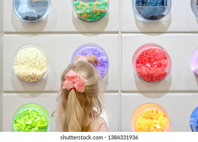 Gurnee, IL/USA - 04-27-2019:  Backview of little girl with long blonde hair choosing legos from colorful selection at the Lego store