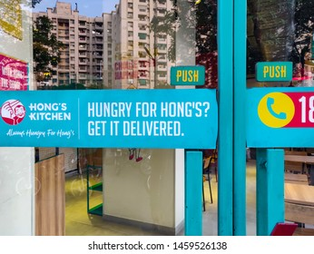 Gurugram, Haryana, India - 07/17/2019: Exterior of asian restaurant blue shop glass door close up, warmly lit inside. Hong's kitchen by Jubilant FoodWorks company. Reflection of apartment building.