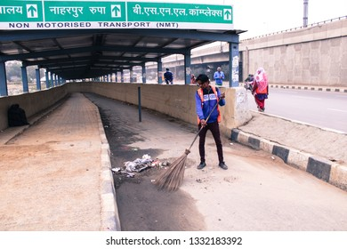 GURUGRAM, HARYANA, INDIA - FEB 14, 2019: indian municipal worker sweep the road in a traditional way broom sticks tied to long bamboo stick on February 14,2019 in Haryana,india, - image
