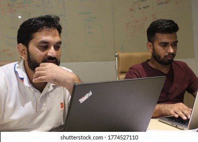 Gurugram, India - July 9, 2018 : A Manager and his Coworker working in office with laptop.