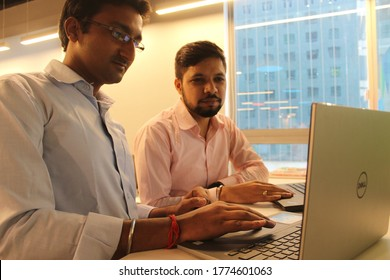 Gurugram, India - July 9, 2018 : Indian Man standing while working in a startup office with laptop.