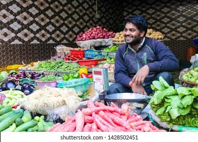 Gurugram/Gurgaon, Haryana, India - 17 may, 2019:   Vegetable vendor laughs at market, cheerful greengrocer selling vegetables .