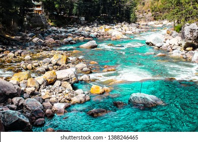 Gushing Parvati river in the snow mountains of Kasol, Himachal Pradesh, India. Cold river water rushing through the magical stones in the valley of gods. Green nature at its best.
