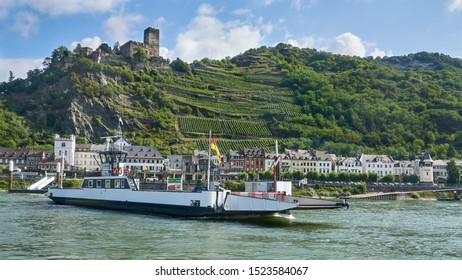 Gutenfels Castle above and a car and passenger ferry crosses the Rhine River below at the medieval town of Kaub, Germany - August 2019.