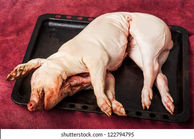gutted Pig being killed at a farm. Pork is on a tray