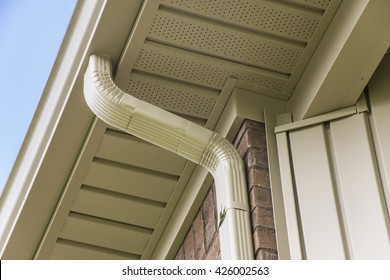 Gutter and downspout near the roof of a house.