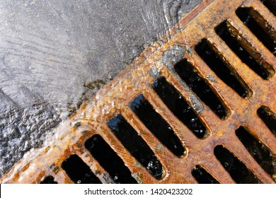 Gutter drain. Storm sewage during rain. Rusty, steel drain cover