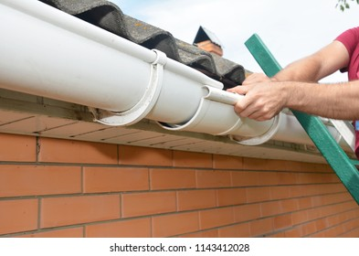 Gutter repair. Roofer contractor installing and repair roof gutter. Guttering repair with hands.
