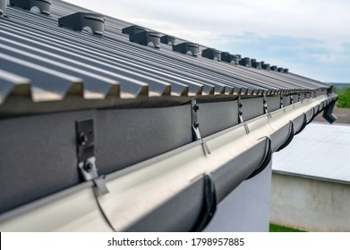 . Gutter system for a metal roof. Holder gutter drainage system on the roof.