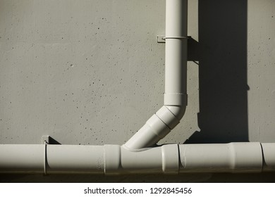 gutter or waterspout or rainspout gray color on gray wall background highlight and shadow with copyspace.