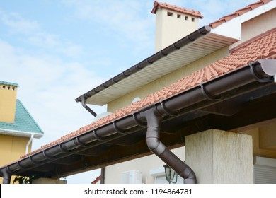 Guttering. Roof gutter pipeline sysem. House rain gutter with holders and downspout pipe.