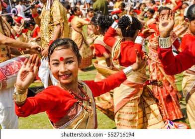 Guwahati, Assam - circa April 2012: Dancing girl in red and yellow sari with red dot on forehead smiles during performance at traditional Bihu festival in Guwahati, Assam. Documentary editorial.