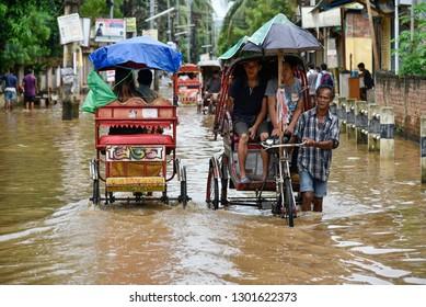 Guwahati, Assam, India. August 24, 2018. Rickshaw pullers transport passengers through waterlogged street after monsoon rainfall, in the Anilnagar area of Guwahati.