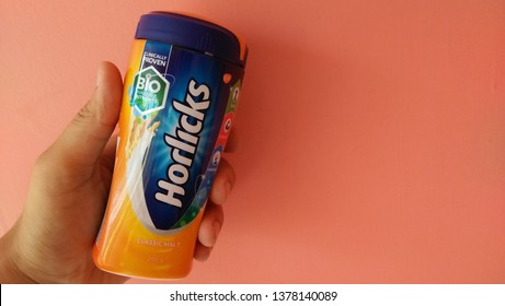 Guwahati, Assam/India-23 April 2019: 200 gram classic malted Horlicks hold by a person isolated on pink background. A malted milk hot drink founded by James and William Horlick