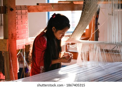 Guwahati, India. 25 November 2020. Student weaving silk and cotton costumes in a traditional method at a manufacturing unit of Parijat Academy in Gauhati.